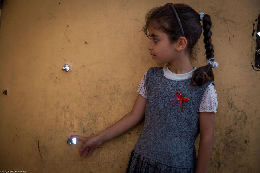 Iracka dziewczynka pokazuje slady po kulach w swoim domu