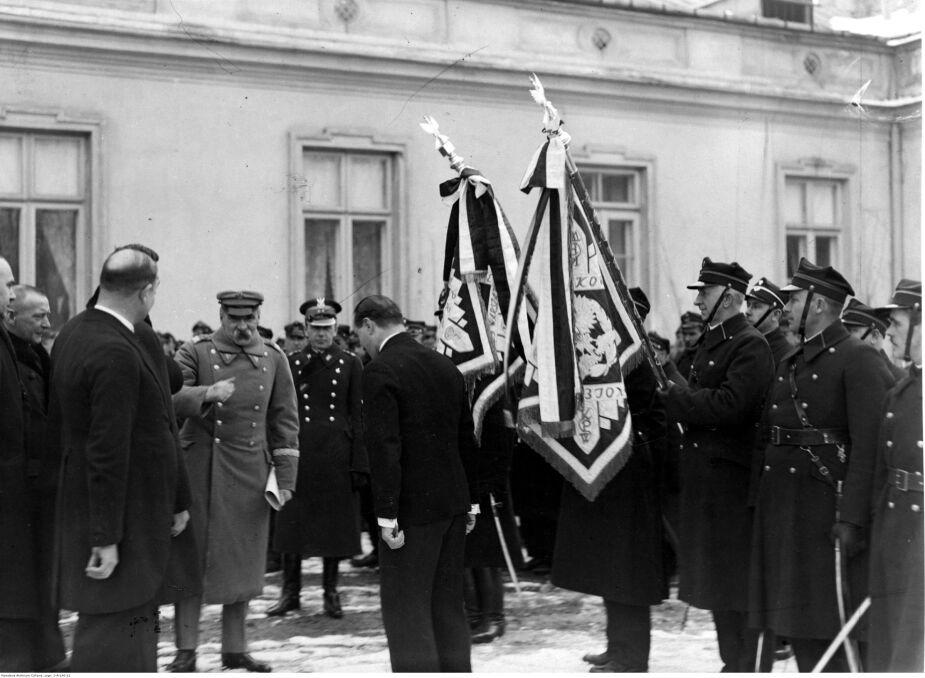 Oddziały Kolejowego Przysposobienia Wojskowego Okręgu Warszawskiego składają życzenia imieninowe Józefowi Piłsudskiemu (trzeci z lewej). Widoczne sztandary oddziałów