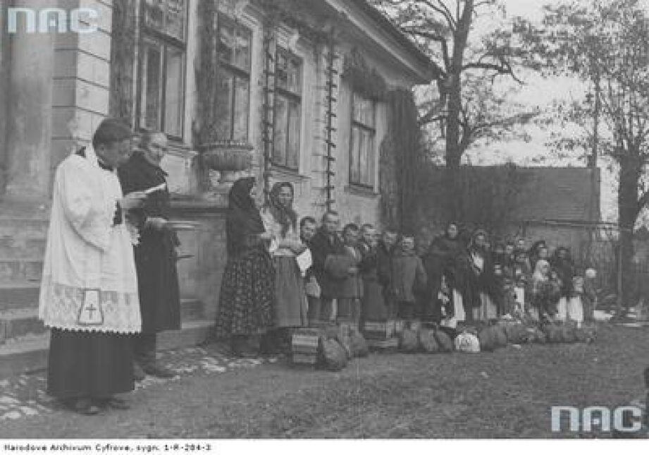 Poświęcenie pokarmów przyniesionych przez mieszkańców wsi przed dworem w Tomaszowicach