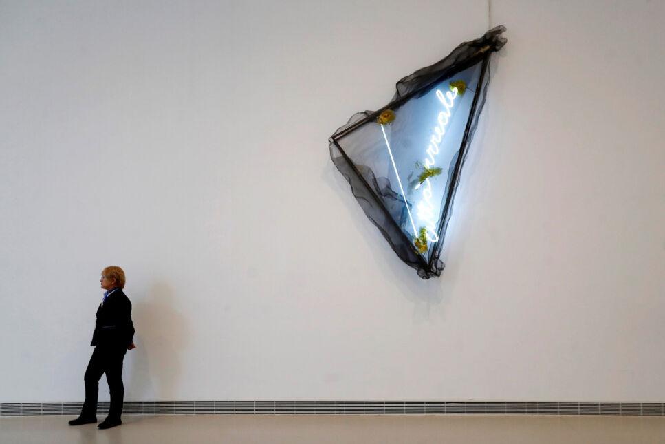 """Pracownik muzeum stoi obok dzieła włoskiego artysty Mario Merza podczas retrospektywnej wystawy """"Time is Mute"""", Muzeum Reina Sofia w Madrycie, Hiszpania"""