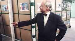 Jerzy Hamerski na tle ruchomych ścian w foyer szkoły