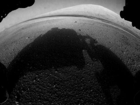 Widok z jednej z kamer z łazika (Hazard-Avoidance cameras). Widać cień samego łazika i górę Mount Sharp w oddali